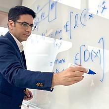 Feizi writing equations on white board.